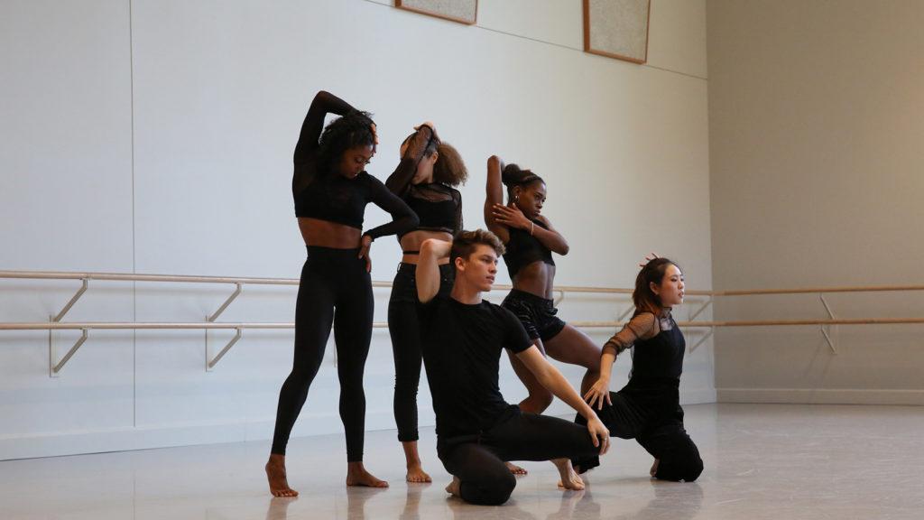 five dancers wearing black pose in a dance studio