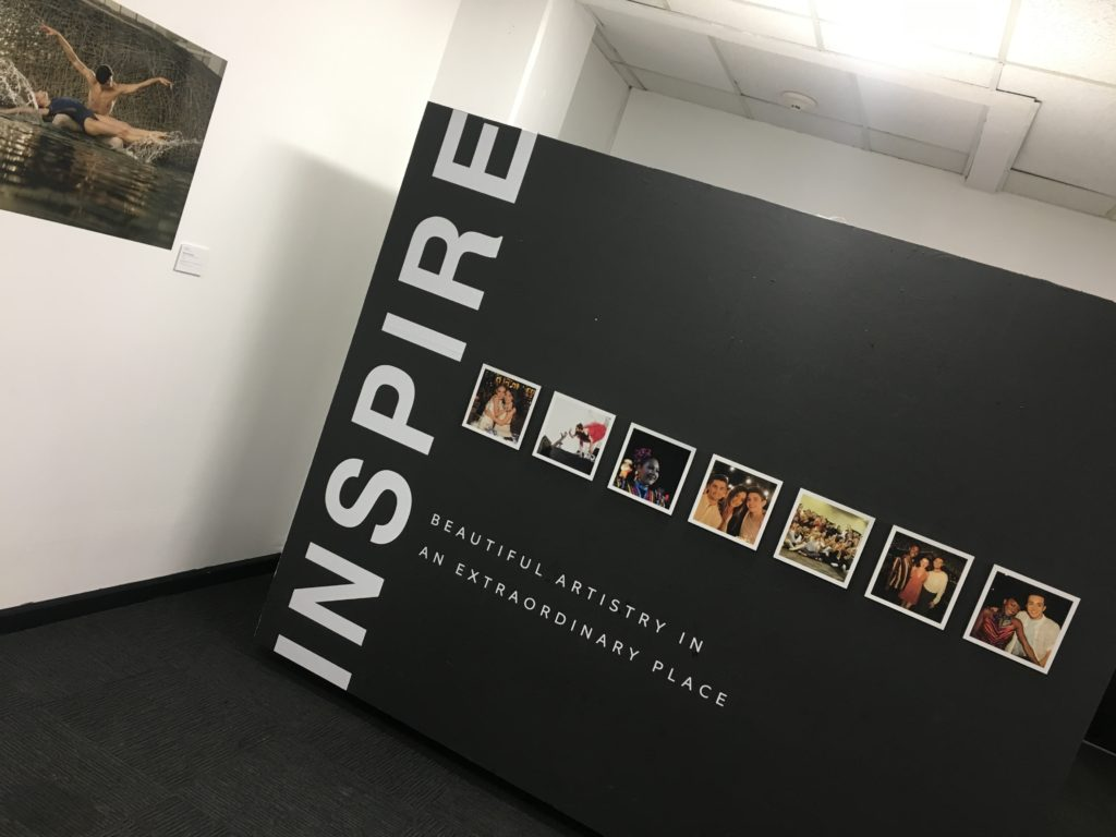 """A black wall with the word """"inspire"""" along with dance photos"""