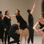 Dancers stand in a vertical line, making various geometric shapes with their bodies