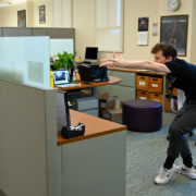 A student dances in a cubicle
