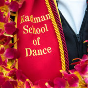 Cardinal sash with gold lettering and colorful lei