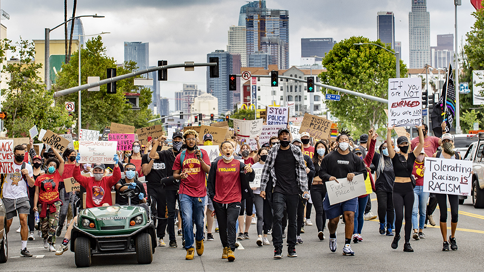 students wearing USC gear march for Black Lives Matter with LA skyline in background