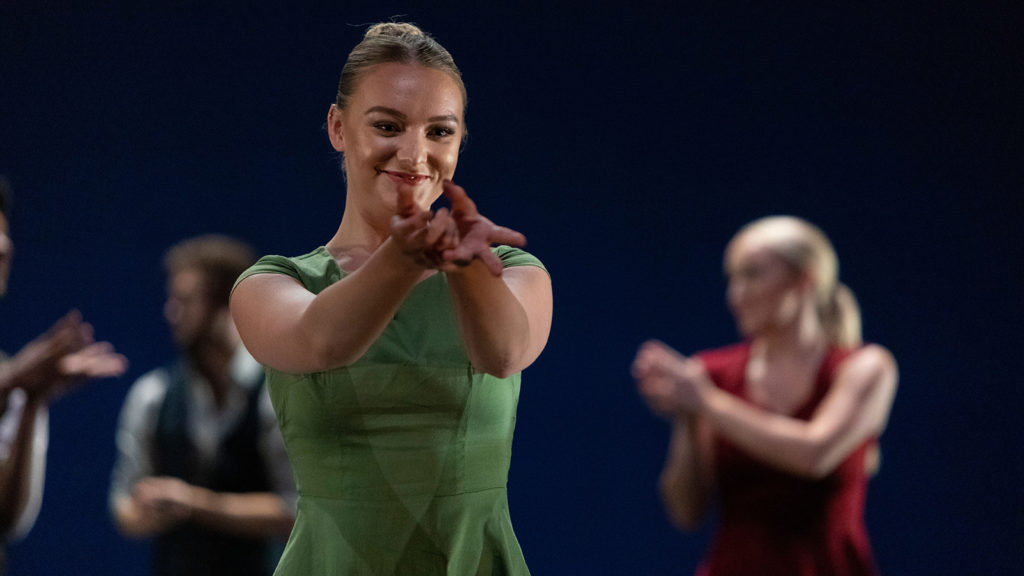 Whitney Hester dancing in a green dress.