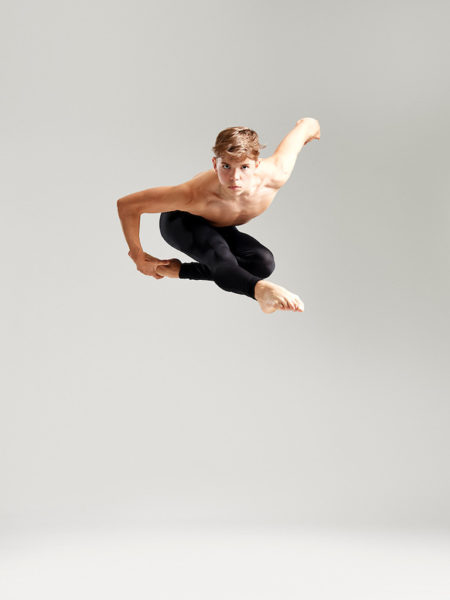 Sebastian Bustamante leaping in front of white background