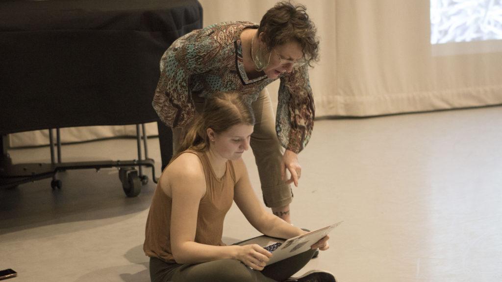 India Dobbie working on a laptop with Professor Dawn Stoppiello
