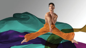 Benjamin Peralta jumping in front of multi colored fabric