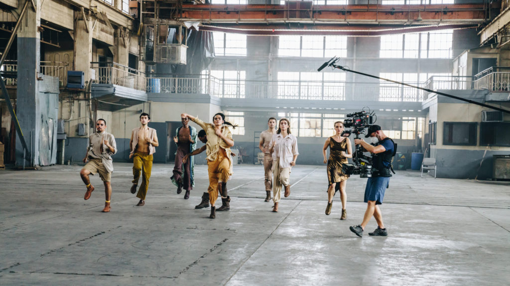 Dancers being filmed in a warehouse