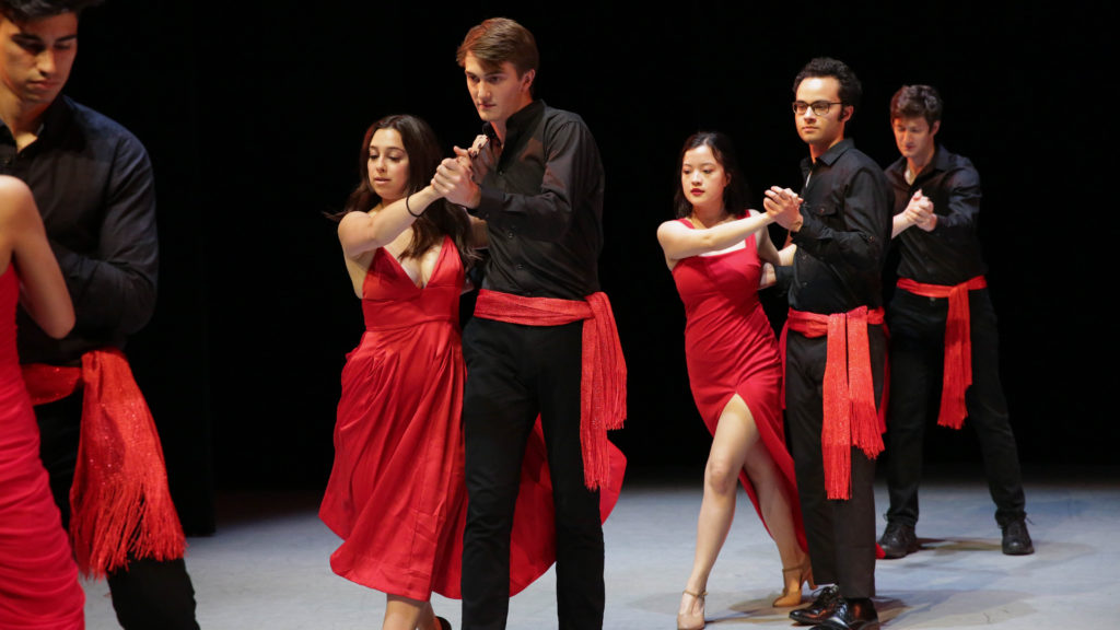 Students dresses in black and red perform on the USC Kaufman stage