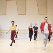 Dancers walking forward in a studio during a commercial dance class