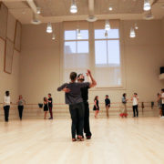 Jay Fuentes and partner demonstrate a ballroom move in the middle of a dance studio