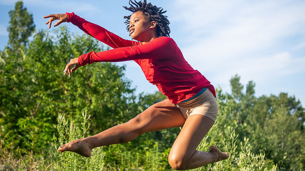 Rachel Harris jumping in front of green trees and blue skies