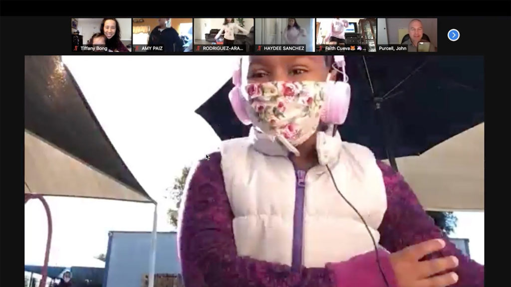 Zoom screenshot of student dancing wearing a floral mask and pink headphones