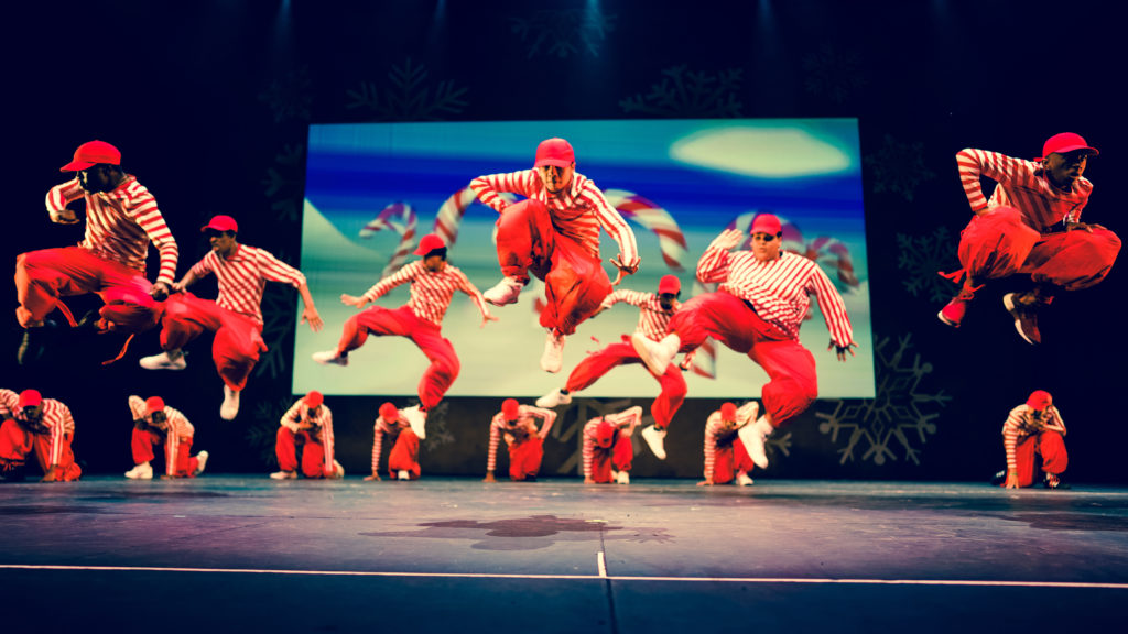 Dancers in red outfits jumping on stage