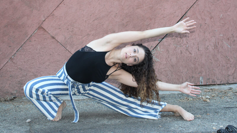Aurora Vaughan lunging with arms stretched out to the side wearing a black tank and blue and white striped pants