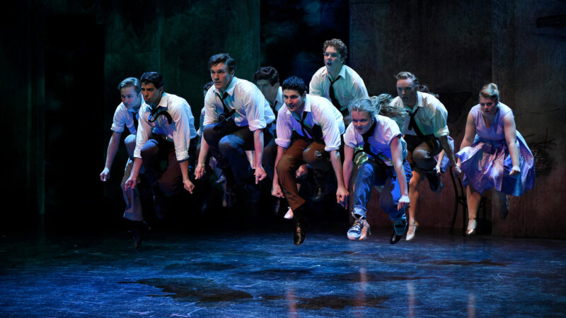 Dancers wearing white button down shirts and black ties jumping in unison