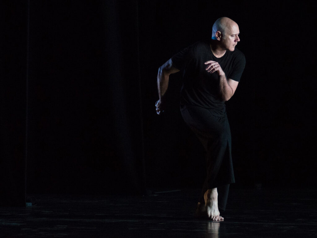 Doug Varone wearing all black dancing barefoot in front of a black background