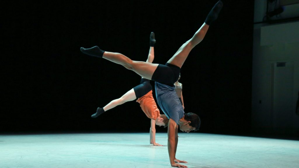 two dancers doing handstands on stage
