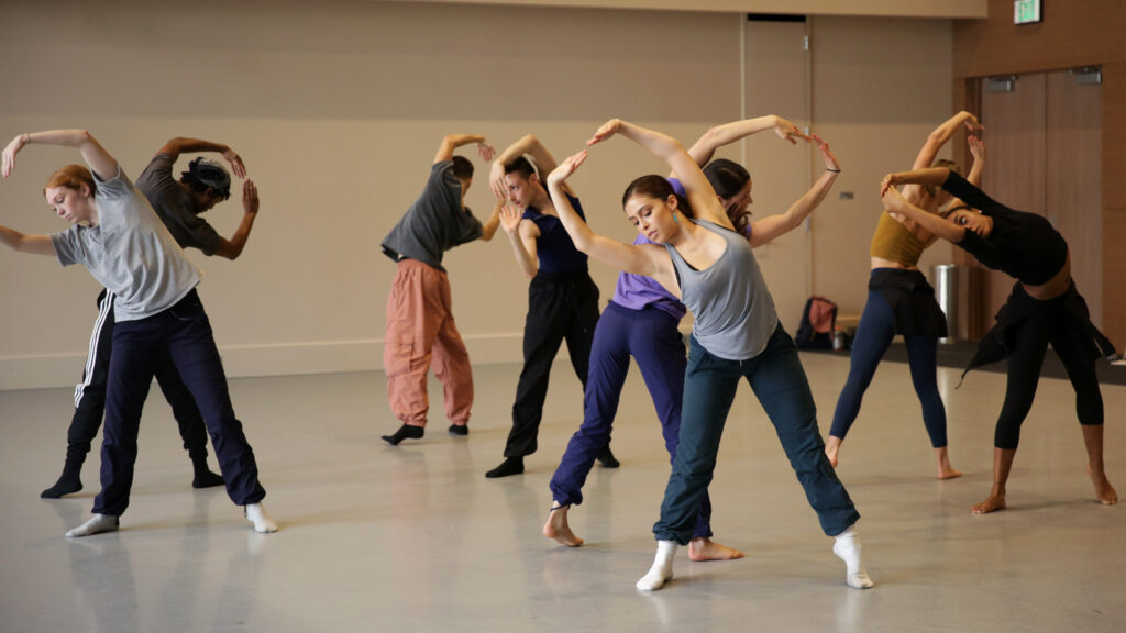 dancers in a studio on tiptoes with rounded arms