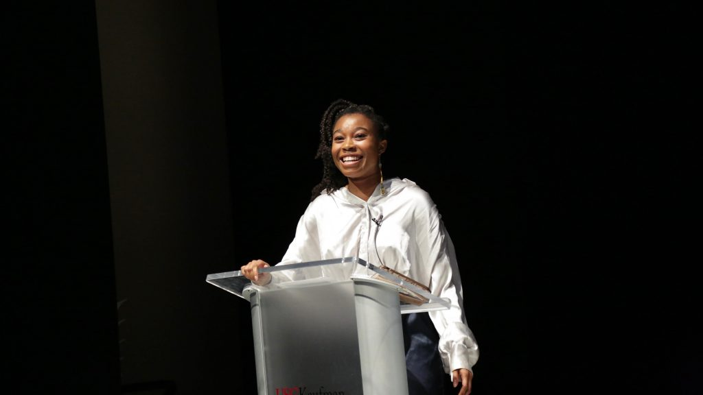 A woman wears a white windbreaker jacket and stands behind a podium giving a presentation