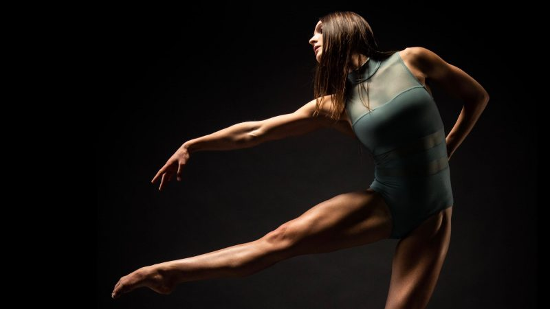 A girl in a green leotard points her arm and leg to the left of the frame
