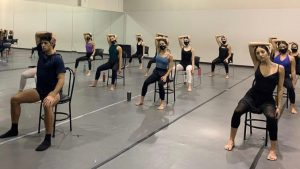 Dancers sit on chairs in a studio and stretch their necks