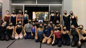 Dance students wearing masks gather around a computer screen and pose for a photo