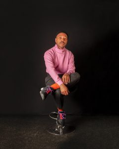 A man in a pink turtleneck sweater sits cross-legged on a stool.