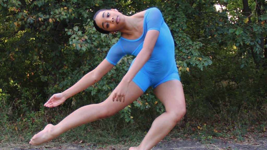 Londyn Alexander dancing barefoot wearing a light blue short sleeved unitard in front of trees