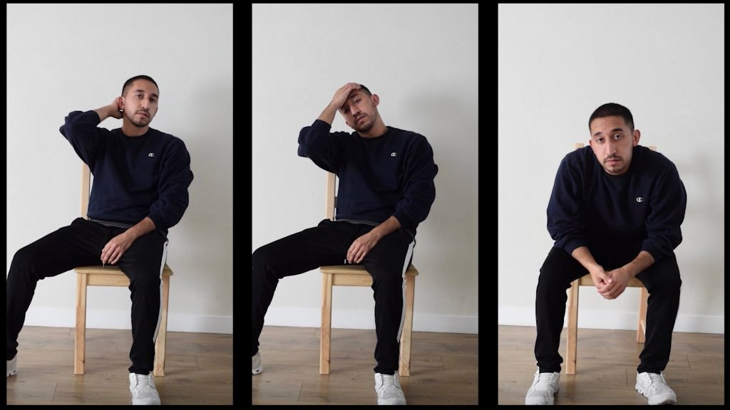 A man sits in the same chair in three poses wearing a black sweatshirt and pants.