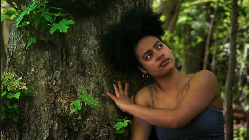A woman wearing a gray tank top leans against a brown tree trunk with bright green leaves.