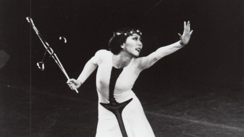 A woman wearing a black and white dress stands on stage and reaches out her hand while she looks beyond it.