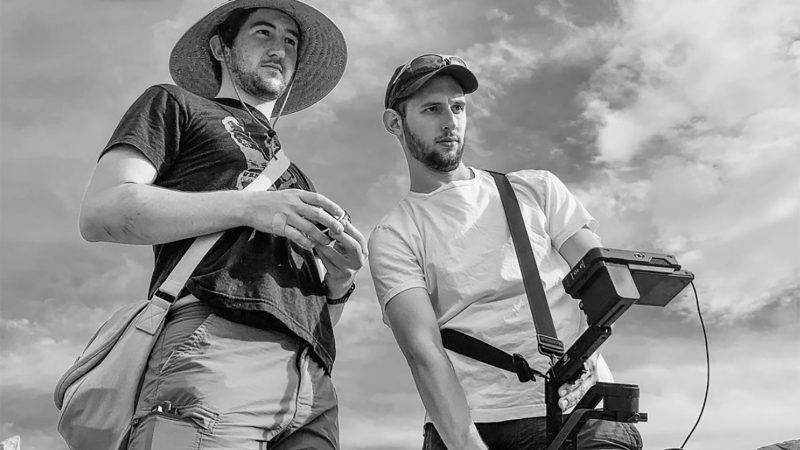Black and white photo of Justin Epstein and Adam Agostino behind the scenes of a film shoot