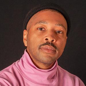 Headshot of Kyle Abraham wearing a black hat and pink turtleneck