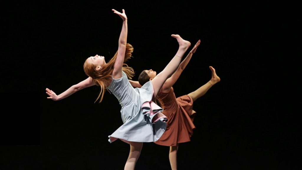 A female dancer in the foreground wears a blue dress and kicks in the air. A second female dancer in the background wears a brown dress and kicks in the air.