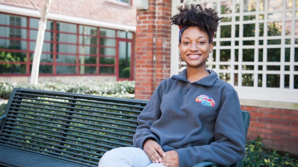 A woman sits on a green bench in front of a brick trellis. She is wearing a gray sweatshirt with the logo of Change the Stigma, which is shaped like a brain.