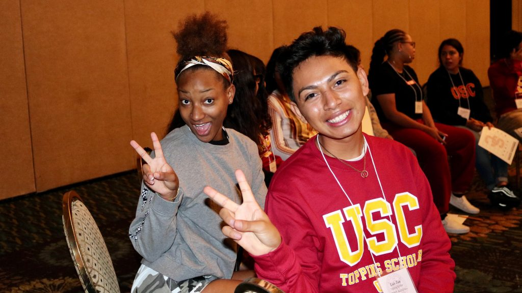 A woman in a gray sweatshirt and a man in a red USC sweatshirt with yellow lettering pose for the camera holding up peace signs with their fingers.
