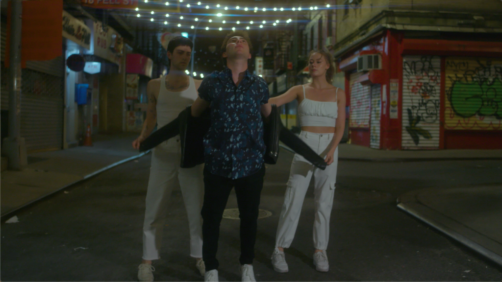 Two men and one woman stand in a triangle formation on a city street. The two dancers wearing white help the central male dancer take off his black leather jacket.