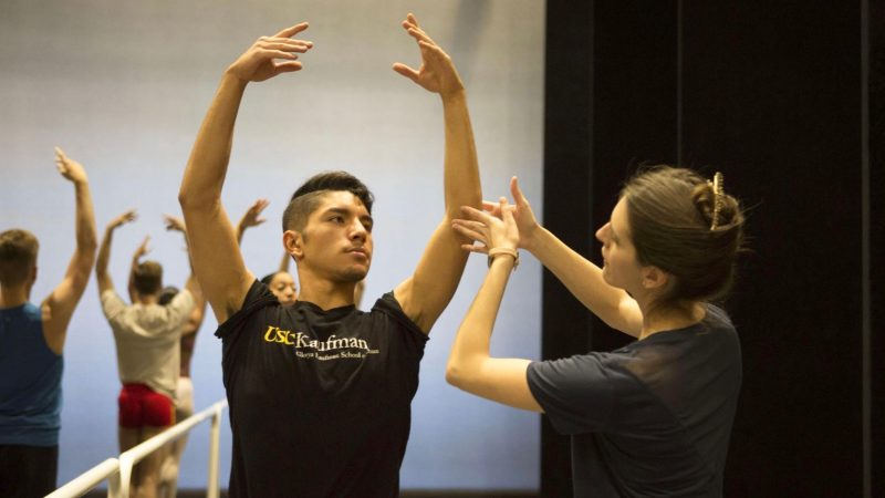 A woman wearing a black shirt guides a male ballet dancer's arms above his head.