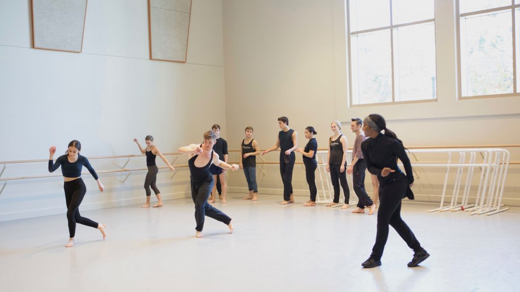 A woman in all black teaches dance students in a large, bright studio space.
