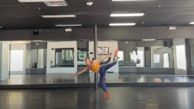 A dancer wearing an orange tank top and blue pants lifts their leg over their head and reaches their hand to the ground.