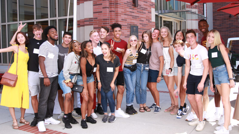 group of students pose and smile in front of brick building