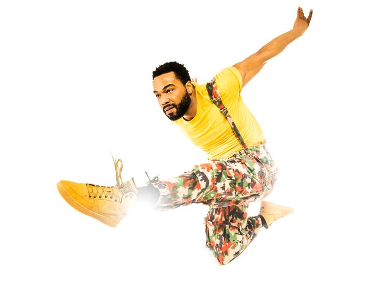 Grasan Kingsberry jumping wearing a yellow t-shirt and camoflauge pants