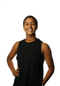 A person wearing a black tank top stands with her hand on her hip as they smile.