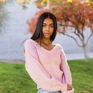 A woman with long, dark hair wearing a pink sweater and light blue jeans looks at the camera in front of grass and a tree with red-orange leaves.
