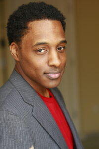 person photographed for headshot in grey tuxedo with red shirt underneath looking to the camera