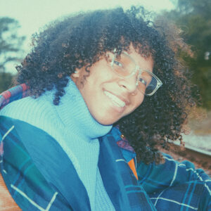 a person with brown curly hair and glasses on smiling over their shoulder with a turtle neck and jacket on