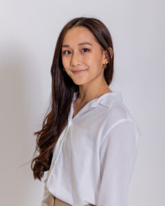 A woman with long, dark hair wearing a white blouse smiles at the camera in front of a white background.