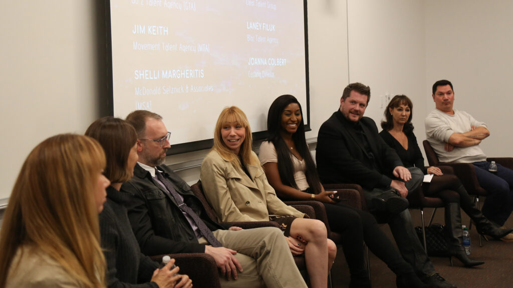 panel of people sitting in chairs and smiling in front of a white board