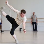 A man in a white shirt and black pants kicks his leg in the air in a dance studio.