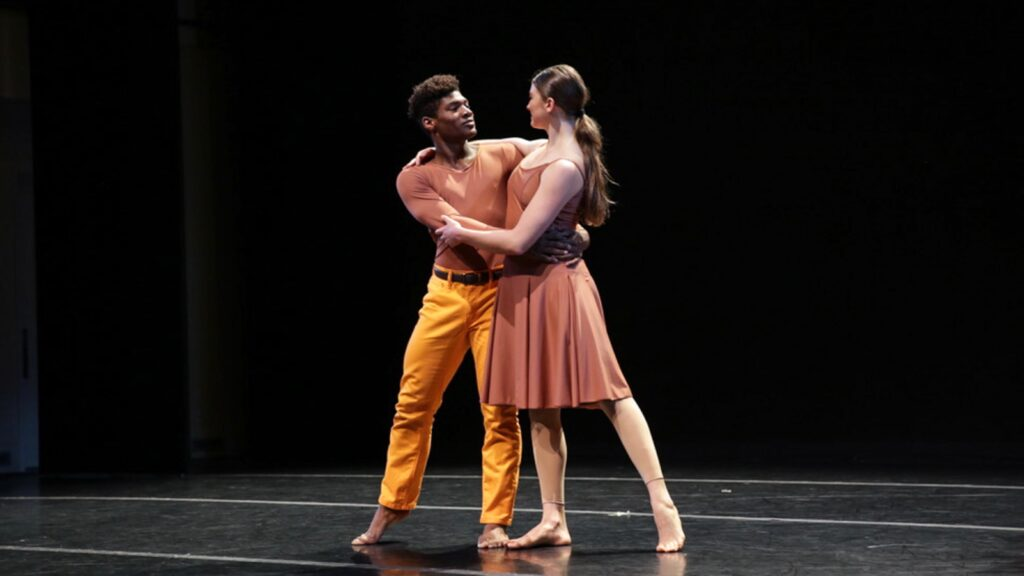 A man in a pale red shirt and orange pants embraces a woman on stage with a low ponytail wearing a pale red dress.